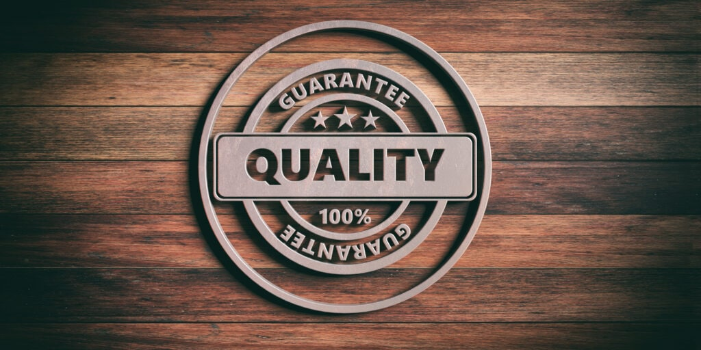QUALITY badge. Round metal sign with text quality on wooden background. 3d illustration